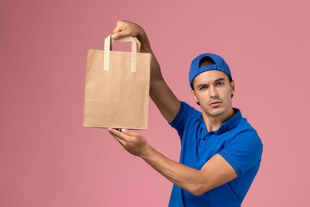 Junger männlicher kurier der vorderansicht in blauer uniform und umhang mit lieferpapierpaket auf seinen händen an der rosa wand
