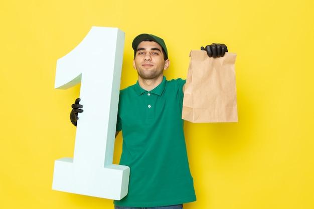 Junger männlicher kurier der vorderansicht in den schwarzen handschuhen der grünen kappe des grünen hemdes, die paket und nummer eins auf gelb halten