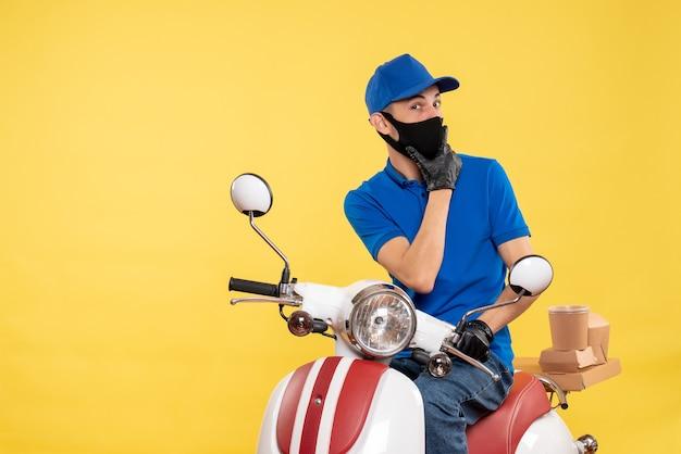 Junger männlicher kurier der vorderansicht in der blauen uniform auf gelbem hintergrund