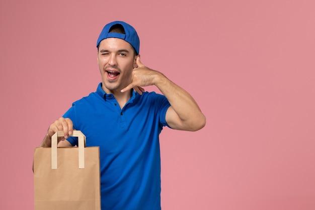 Junger männlicher kurier der vorderansicht in der blauen uniform und im umhang mit papierlieferpaket auf seinen händen auf rosa wand
