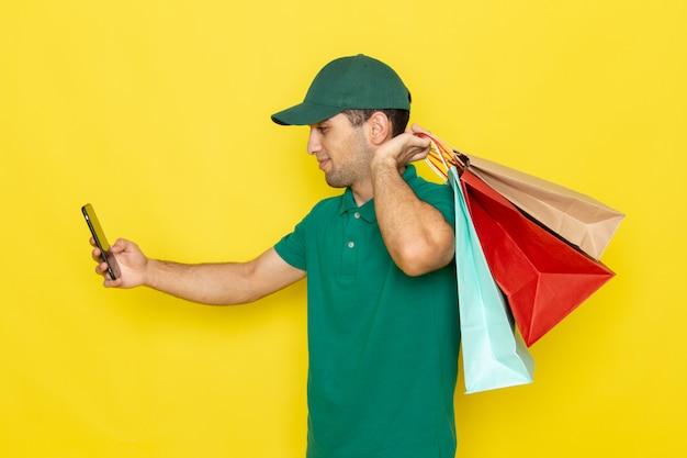 Junger männlicher kurier der vorderansicht in der grünen kappe des grünen hemdes, die einkaufspakete hält und ein telefon verwendet