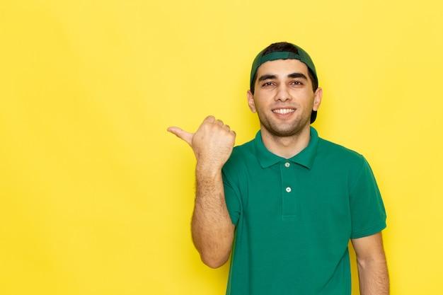 Junger männlicher kurier der vorderansicht in der grünen kappe des grünen hemdes, die lächelt und seinen finger auf den gelben hintergrundjob zeigt, der dienstfarbe liefert
