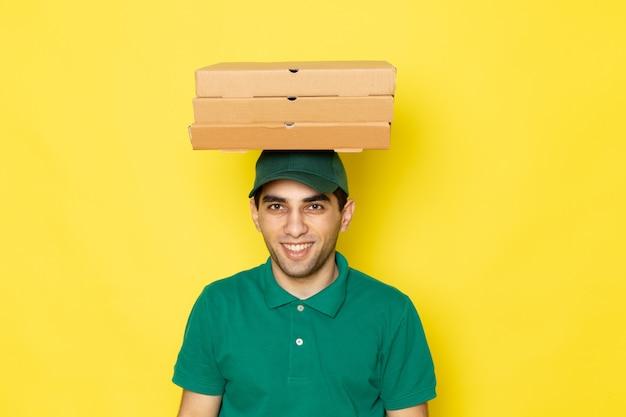 Junger männlicher kurier der vorderansicht in der grünen kappe des grünen hemdes, die lieferkästen auf seinem kopf auf gelb hält