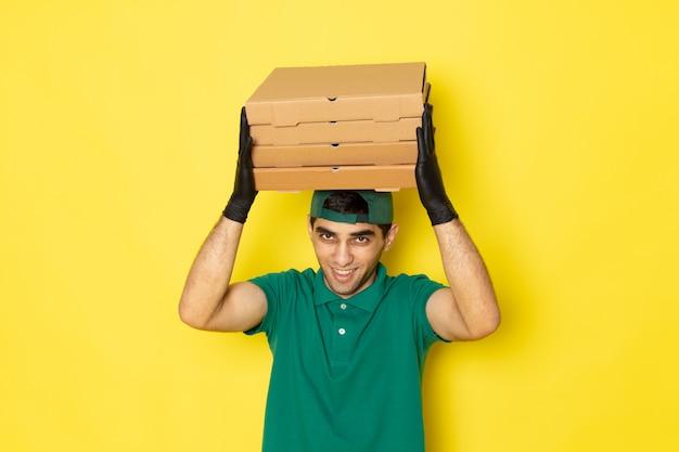 Junger männlicher kurier der vorderansicht in der grünen kappe des grünen hemdes, die lieferkästen mit lächeln auf gelb hält