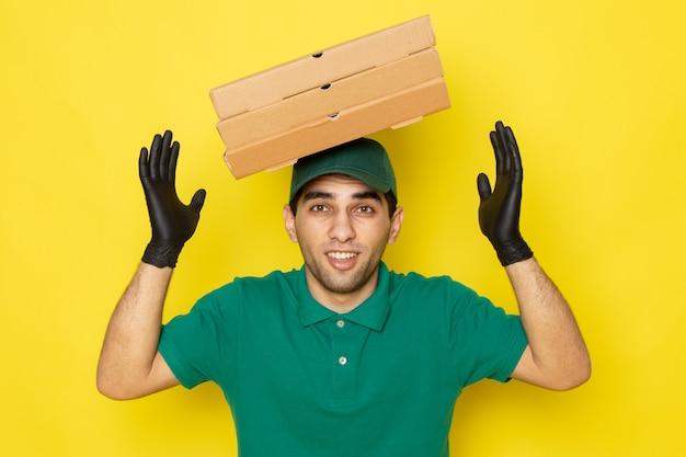 Junger männlicher kurier der vorderansicht in der grünen kappe des grünen hemdes, die lieferkästen mit seinem kopf in den handschuhen auf gelb hält