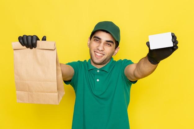 Junger männlicher kurier der vorderansicht in der grünen kappe des grünen hemdes, die lieferpaket und weiße karte auf gelb hält