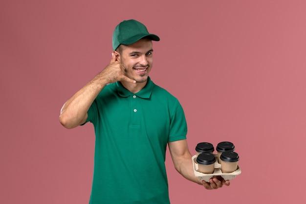 Junger männlicher kurier der vorderansicht in der grünen uniform, die braune kaffeetassen auf hellrosa hintergrund hält