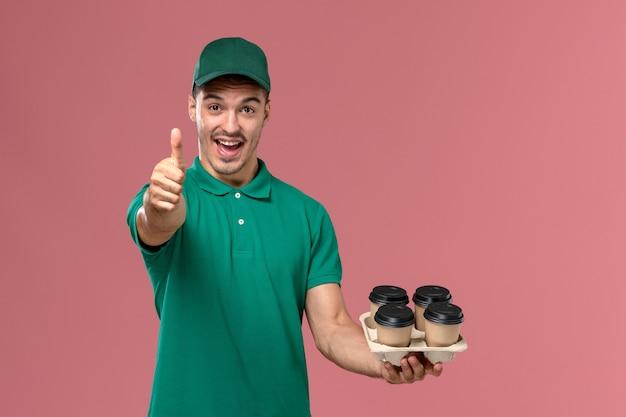 Junger männlicher kurier der vorderansicht in der grünen uniform, die braune kaffeetassen hält, die auf hellrosa hintergrund lachen
