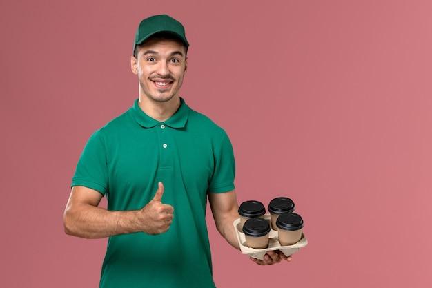 Junger männlicher kurier der vorderansicht in der grünen uniform, die braune kaffeetassen hält, die auf hellrosa hintergrund lächeln