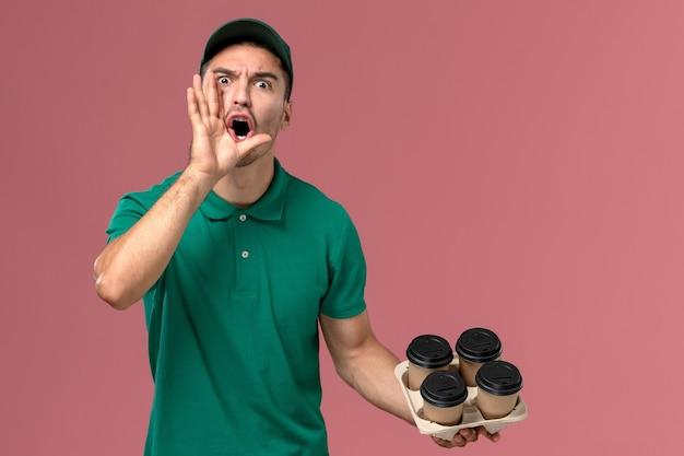 Junger männlicher kurier der vorderansicht in der grünen uniform, die braune kaffeetassen hält, die auf hellrosa hintergrund schreien