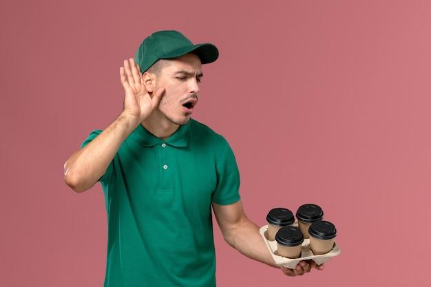 Junger männlicher kurier der vorderansicht in der grünen uniform, die braune kaffeetassen hält, die genau auf hellrosa hintergrund hören
