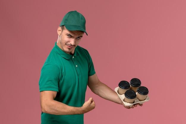 Junger männlicher kurier der vorderansicht in der grünen uniform, die braune kaffeetassen lustig biegend auf hellrosa hintergrund hält