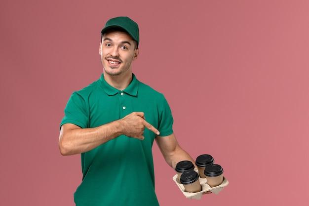 Junger männlicher kurier der vorderansicht in der grünen uniform, die kaffeetassen hält, die auf hellrosa hintergrund lächeln
