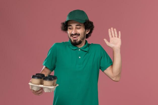 Junger männlicher kurier der vorderansicht in der grünen uniform und im umhang, die braune lieferkaffeetassen auf hellrosa hintergrunddienstuniform-lieferarbeiter halten