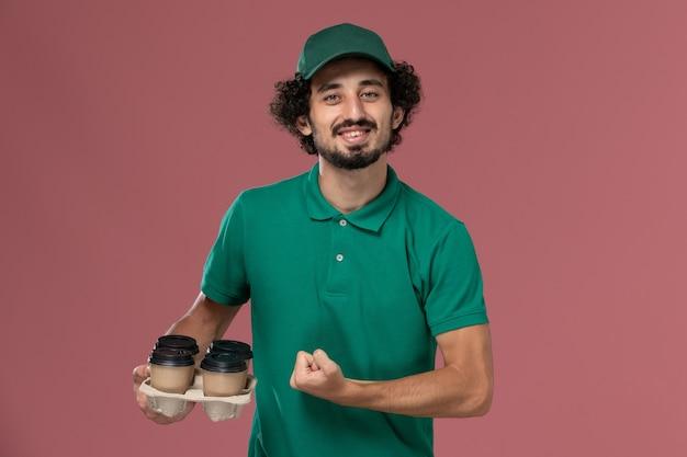 Junger männlicher kurier der vorderansicht in der grünen uniform und im umhang, die braune lieferkaffeetassen halten, die auf dem rosa hintergrunddienstuniform-lieferarbeiterjob beugen