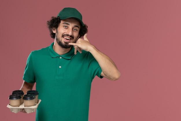 Junger männlicher kurier der vorderansicht in der grünen uniform und im umhang, die braune lieferkaffeetassen halten, die auf der rosa hintergrunddienstuniformlieferungsarbeit lächeln
