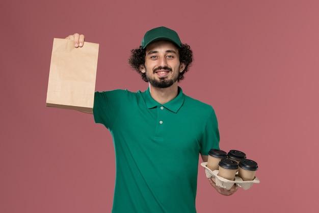 Junger männlicher kurier der vorderansicht in der grünen uniform und im umhang, die lieferkaffeetassen mit lebensmittelpaket auf rosa hintergrunddienstuniformlieferung halten