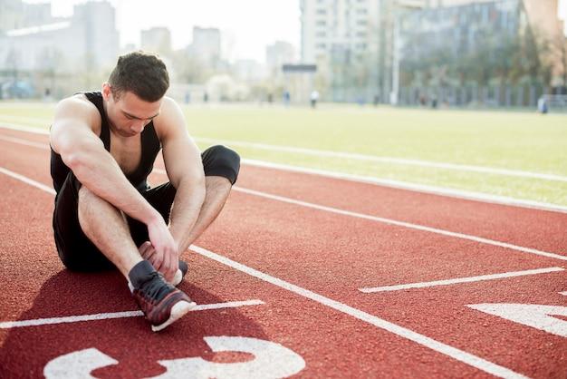 Junger männlicher läufer, der auf der rennstrecke betrachtet seine schuhe sitzt