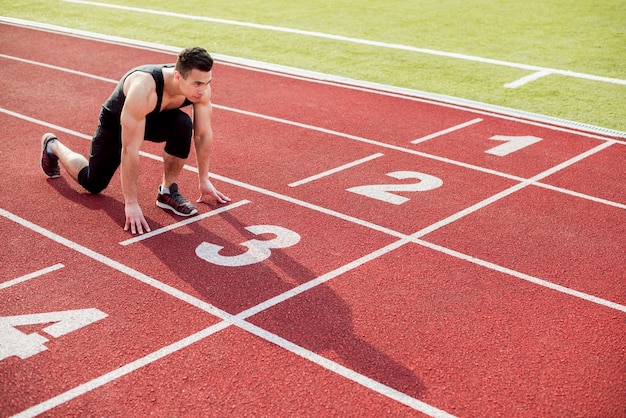 Junger männlicher läufer, der bereit ist, position auf rennstrecke zu beginnen