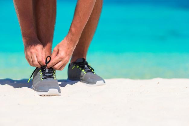 Junger männlicher läufer, der fertig wird, auf weißem strand zu beginnen