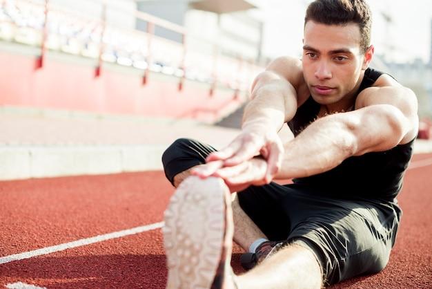 Junger männlicher läufer, der ihre hände beim trainieren am stadion ausdehnt