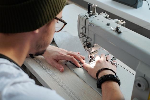 Junger männlicher lederarbeiter, der durch elektrische nähmaschine in der werkstatt sitzt, während er neue lederbrieftasche oder anderen gegenstand macht