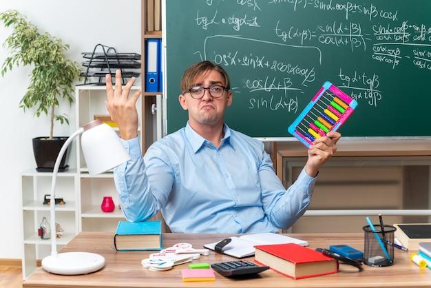 Junger männlicher lehrer, der brillen mit rechnungen trägt, die verwirrt schauen, bereiten lektion vor, die am schulschreibtisch mit büchern und notizen vor tafel im klassenzimmer sitzt