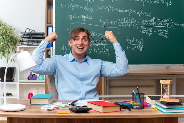 Junger männlicher lehrer, der eine brille hält, die glücklich und aufgeregt die fäuste hebt, die an der schulbank mit büchern und notizen vor der tafel im klassenzimmer sitzen