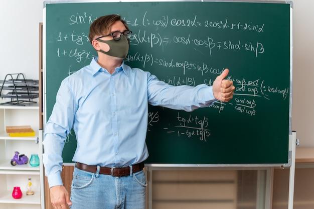 Junger männlicher lehrer mit brille in gesichtsschutzmaske erklärt die lektion und zeigt daumen hoch, die in der nähe der tafel mit mathematischen formeln im klassenzimmer stehen