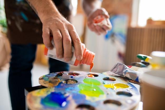 Junger männlicher maler, der gouache der orange farbe in palette hinzufügt, bevor farben während der arbeit im studio gemischt werden