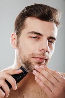 Junger männlicher mann, der die kamera zu hause ausgezogen und lokalisiert wird, hautpflege beim rasieren seines gesichtes mit trimmer gegen graue wand habend betrachtet
