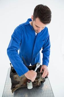 Junger männlicher mechaniker, der automotor repariert