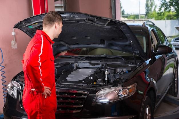 Junger männlicher motormechaniker in uniform, der nahe einer schwarzen limousine steht