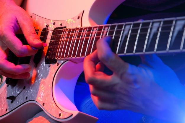 Junger männlicher musiker mit einer weißen gitarre