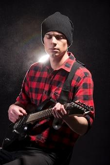 Junger männlicher musiker spielt eine sechssaitige bassgitarre.