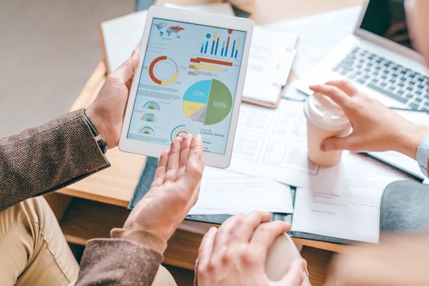 Junger männlicher ökonom mit touchpad, der auf finanzdiagramm auf bildschirm zeigt, während daten dem kollegen erklärt