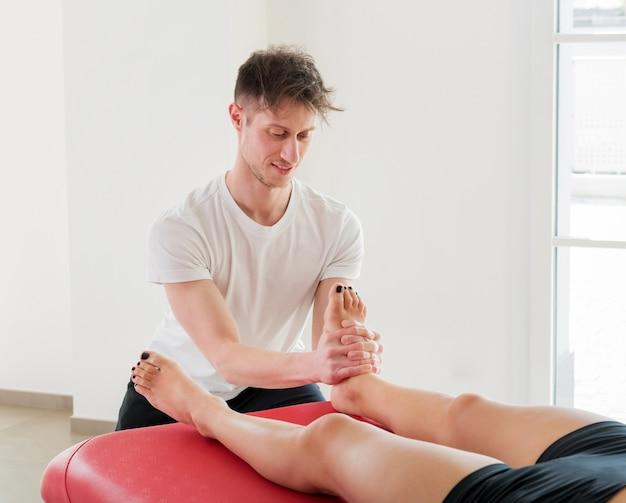 Junger männlicher osteopath, der eine vertrauens-fuß- und knöchelmassage durchführt, die mit den händen druck auf den fußballen ausübt, um verspannungen zu lösen, die durchblutung zu fördern und den patienten zu entspannen