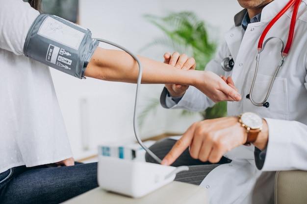Junger männlicher psysician mit messendem blutdruck des patienten