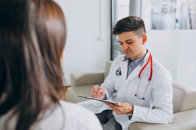 Junger männlicher psysician mit patienten am krankenhaus