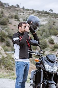 Junger männlicher radfahrer, der auf seinen sturzhelm sich setzt, um sein motorrad zu fahren