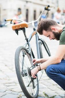 Junger männlicher radfahrer, der sein fahrrad repariert