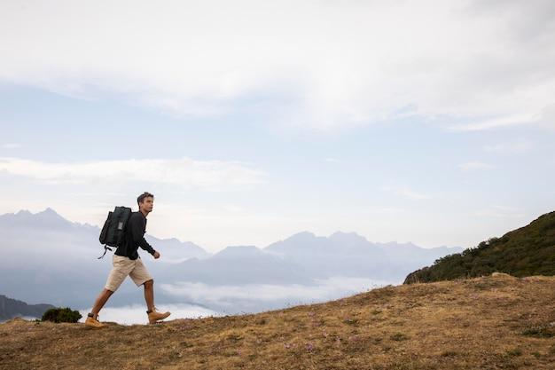 Junger männlicher reisender, der alleine mit kopienraum wandert