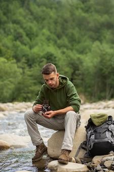 Junger männlicher reisender, der die ländliche umgebung genießt