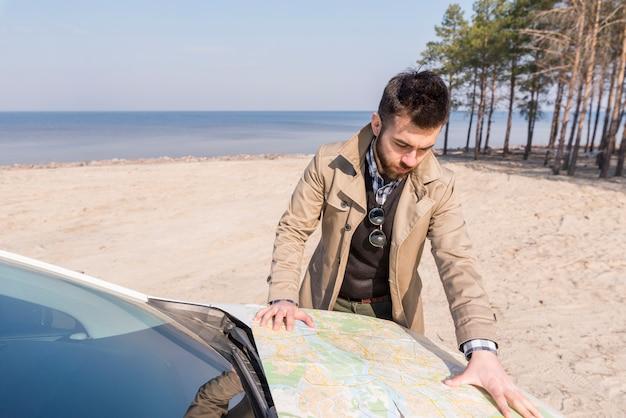 Junger männlicher reisender, der nach dem standort auf karte über der automütze am strand sucht