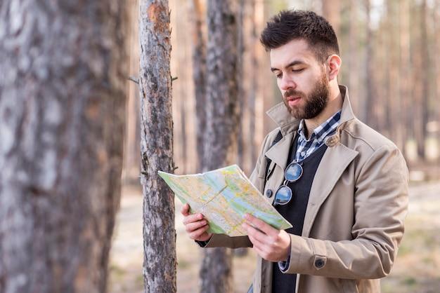 Junger männlicher reisender, der nach dem standort in der karte sucht