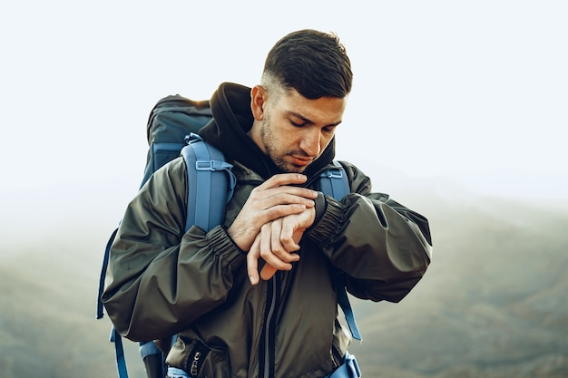 Junger männlicher reisender, der sein nahes porträt der intelligenten uhr betrachtet