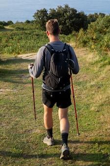 Junger männlicher reisender, der wandern geht