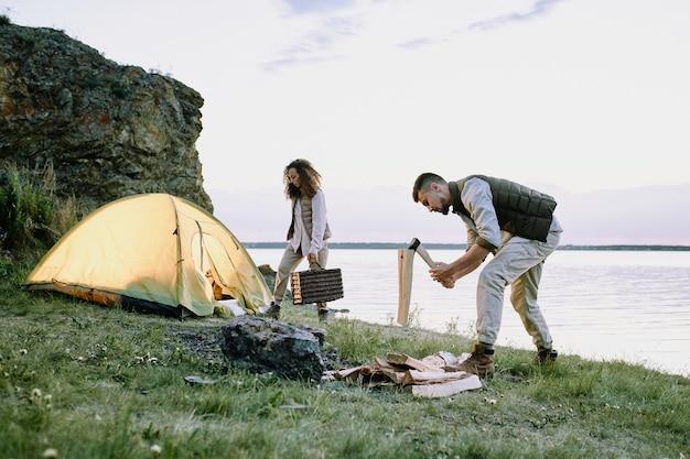 Junger männlicher reisender mit axt, die holz am flussufer hackt, bedeckt durch grünes gras auf hintergrund seiner frau und ihres zeltes
