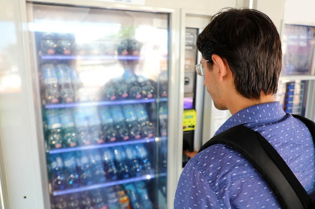 Junger männlicher rucksacktourist, der einen snack oder ein getränk am automaten wählt