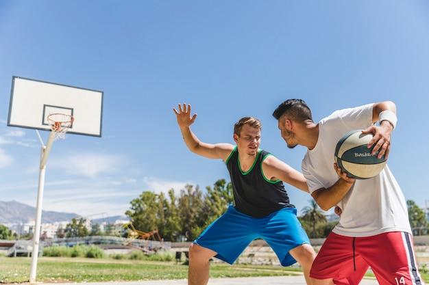 Junger männlicher spieler, der mit basketball-spieler spielt